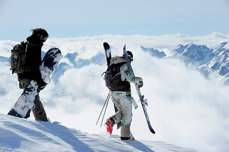 Skier and snowboarder preparing to carve.