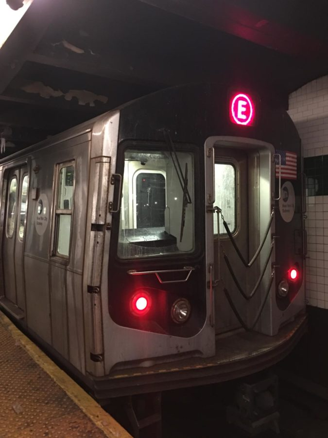 A view of the back of a subway as it begins to depart the station.
