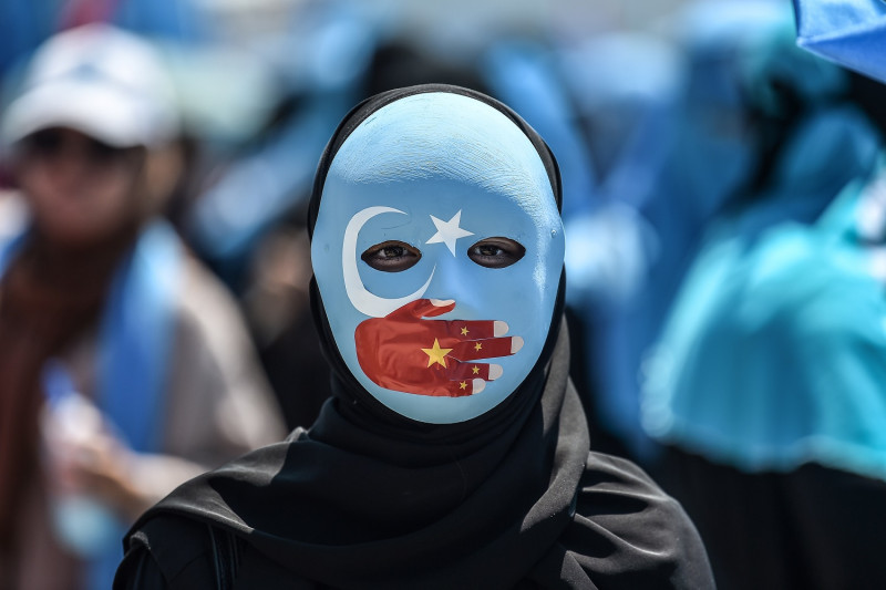 TOPSHOT+-+A+demonstrator+wearing+a+mask+painted+with+the+colours+of+the+flag+of+East+Turkestan+and+a+hand+bearing+the+colours+of+the+Chinese+flag+attends+a+protest+of+supporters+of+the+mostly+Muslim+Uighur+minority+and+Turkish+nationalists+to+denounce+China%27s+treatment+of+ethnic+Uighur+Muslims+during+a+deadly+riot+in+July+2009+in+Urumqi%2C+in+front+of+the+Chinese+consulate+in+Istanbul%2C+on+July+5%2C+2018.+-+Nearly+200+people+died+during+a+series+of+violent+riots+that+broke+out+on+July+5%2C+2009+over+several+days+in+Urumqi%2C+the+capital+city+of+the+Xinjiang+Uyghur+Autonomous+Region%2C+in+northwestern+China%2C+between+Uyghurs+and+Han+people.+%28Photo+by+OZAN+KOSE+%2F+AFP%29++++++++%28Photo+credit+should+read+OZAN+KOSE%2FAFP%2FGetty+Images%29