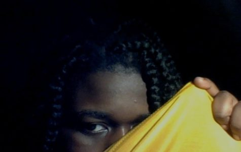 A vibrant, yellow fabric is pulled through the air, obscuring the whole of her mouth, her nose and her right eye. What lies beneath?