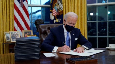 President Biden signs an executive order in the Oval Office.